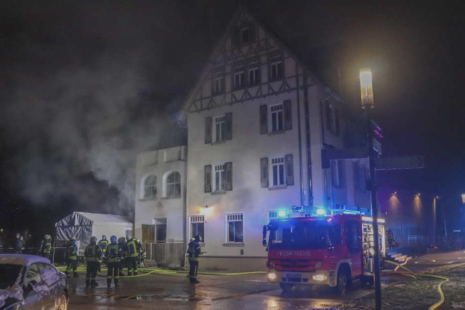 Feuerwehrleute stehen bei Löscharbeiten vor einem Hotel am Remspark in Schwäbisch Gmünd (Ostalbkreis).