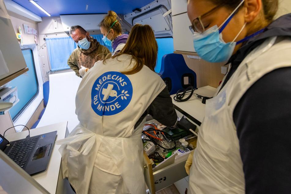 Eine Ärztin (2.v.l.) und zwei Assistentinnen behandeln einen Patienten in einem Behandlungsbus in München.