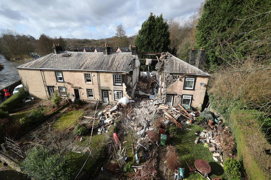 Ein Wohnhaus in der Nähe von Manchester ist durch eine Explosion zusammengebrochen und hat eine Frau unter den Trümmern vergraben.