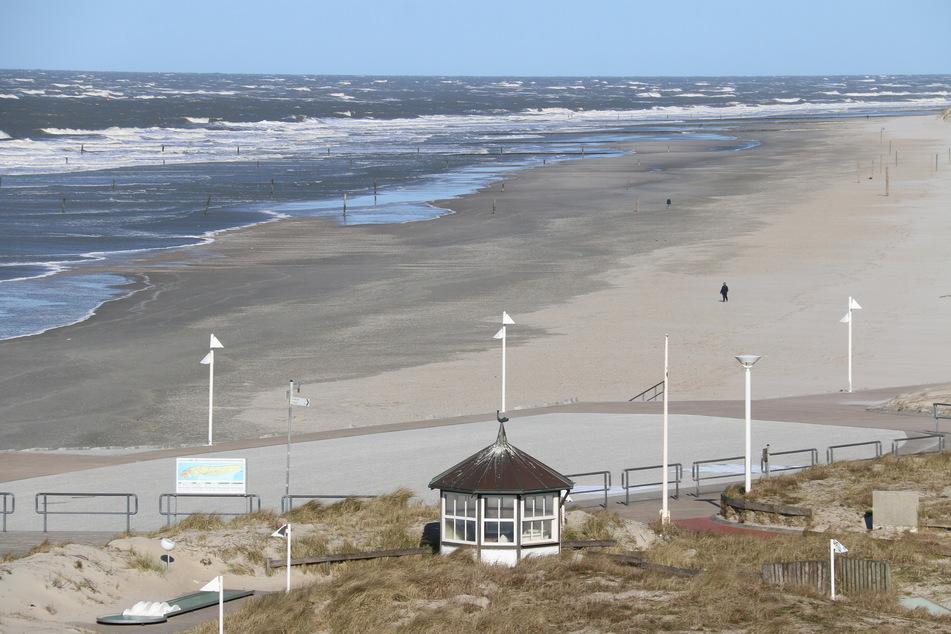Nur vereinzelt gehen Menschen am Strand von Norderney entlang.