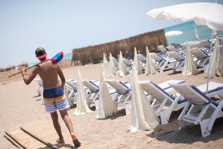 Ein Mann mit einem Besen geht an einem leeren Strand in Antalya entlang. Die Bundesregierung hat die Türkei zusammen mit 130 weiteren Ländern als Corona-Risikogebiet eingestuft.