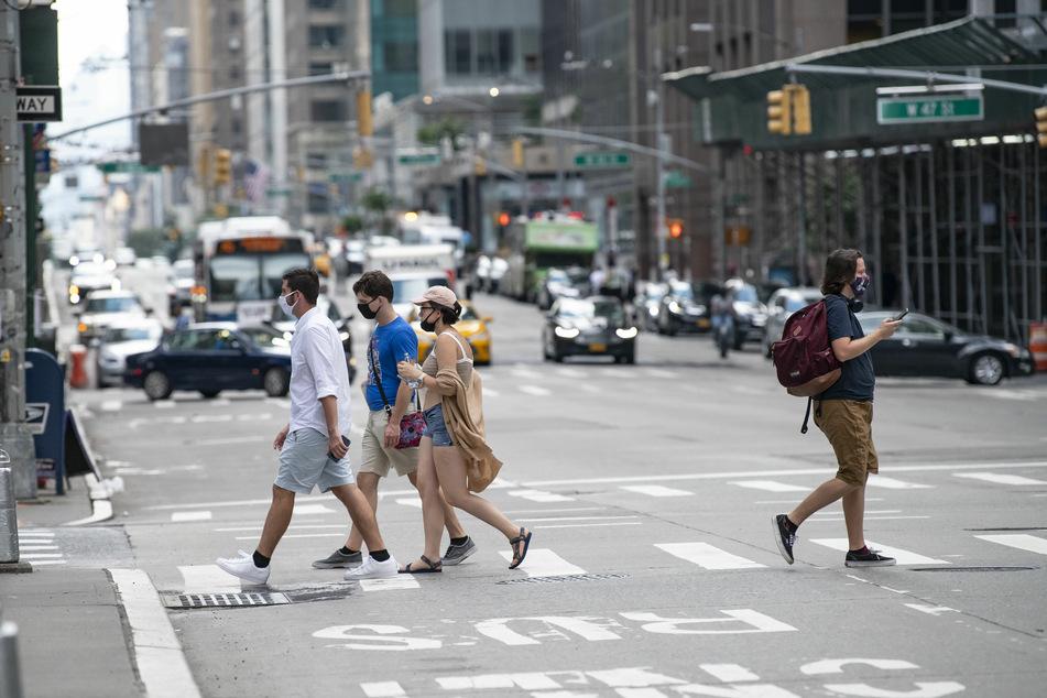 Fußgänger mit Schutzmasken überqueren die 6th Avenue.