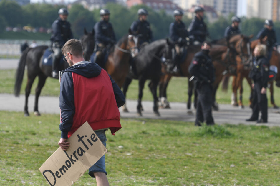 Ein Demo-Teilnehmer geht auf der Theresienwiese an berittener Polizei vorbei.