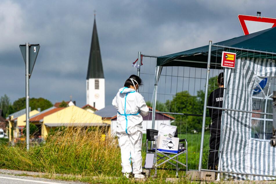 Eine Frau in Schutzkleidung steht nahe eines Bauernhofs. Nach der Corona-Masseninfektion Erntehelfern auf einem Gemüsehof in Mamming will die Staatsregierung am Montag eine Covid-Teststation in der niederbayerischen Gemeinde aufbauen.