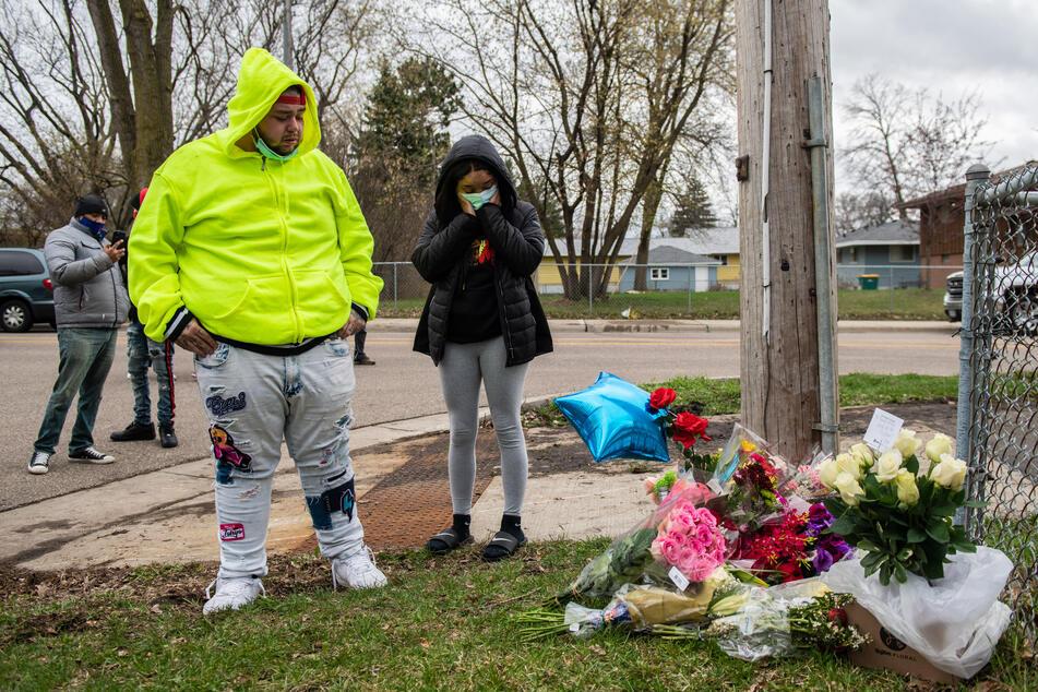 Trauernde am mit Blumen geschmückten Tatort.