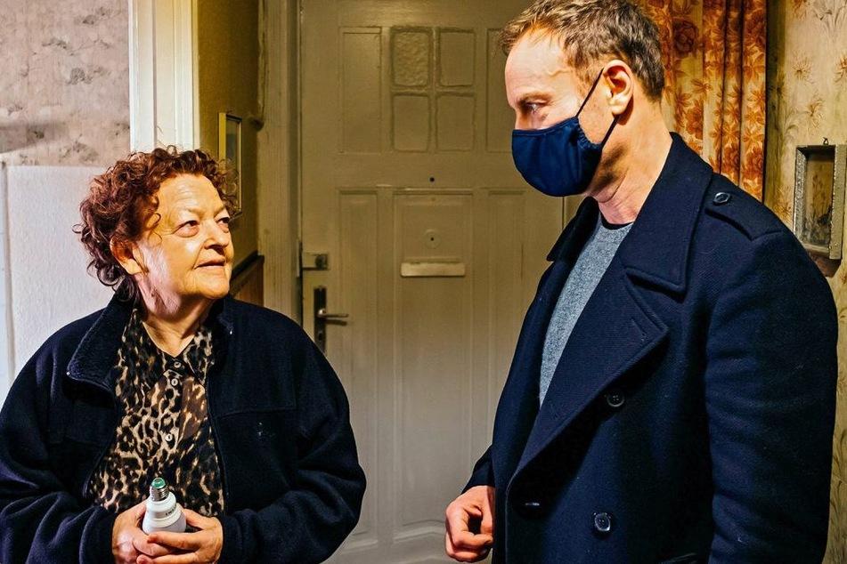 Kriminalhauptkommissar Robert Karow befragt Mieterin Ilse Kirschner (Friederike Frerichs, 77). Die Ermittlungen finden unter Corona-Bedingungen statt, weshalb die Kommissare eine Maske tragen und Abstand halten.