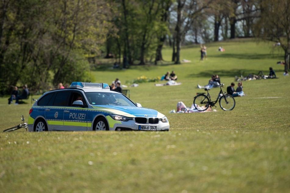 Ein Polizeiwagen fährt am Sonntag bei Sonnenschein durch einen Park am Aachener Weiher. (Symbolbild)