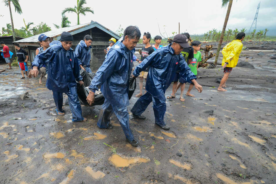 Emergency responders carry the body of a person who was buried in mud after a flood brought by the heavy rains from typhoon Goni in Albay Province, the Philippines.