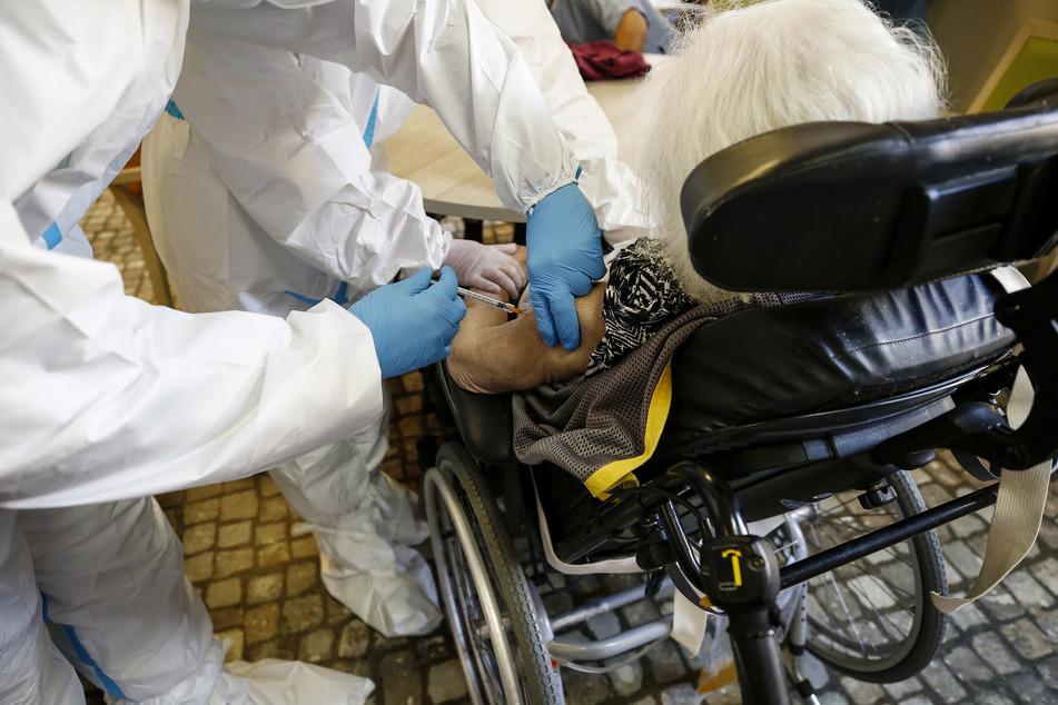 Eine ältere Frau bekommt in einem Pflegeheim eine Impfung mit dem Corona-Impfstoff von Biontech/Pfizer.