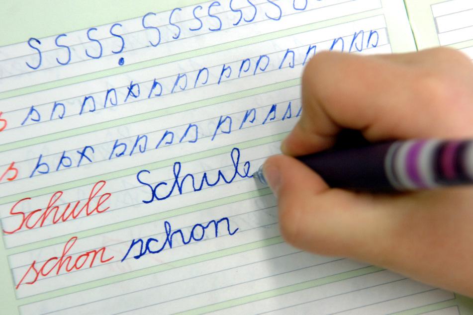 """In einer Dorfschule schreibt ein Mädchen im Unterricht das Wort """"Schule"""" in ihr Heft."""