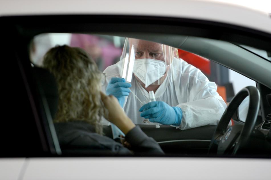 Luxemburg, Bascharage: Ein Medizinischer Mitarbeiter kümmert sich um eine Person, die mit dem Fahrzeug zu einer der Stationen gekommen ist, um sich auf den Coronavirus testen zu lassen.