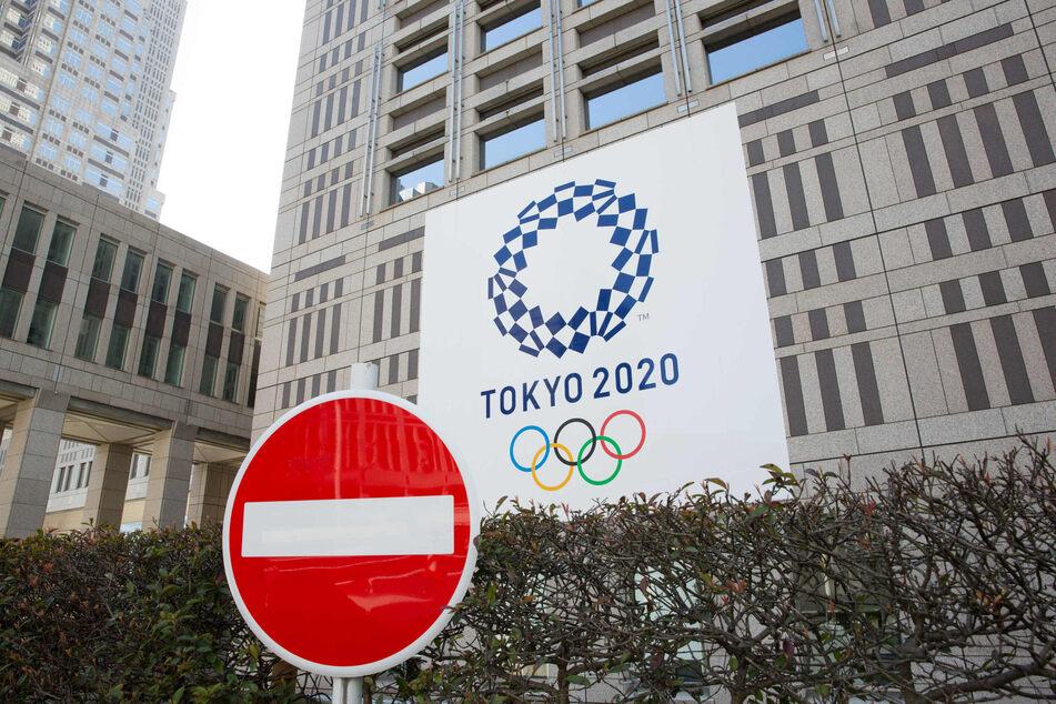 Verkehrsschild mit Verbot der Einfahrt steht vor dem Gebäude der Stadtregierung von Tokio, während im Hintergrund ein Banner mit dem Logo der Olympischen Spiele 2020 in Tokio zu sehen ist.