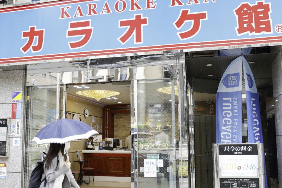 Japan, Tokio: Eine Passantin mit Mundschutz geht an einer wiedereröffneten Karaoke-Lounge vorbei.