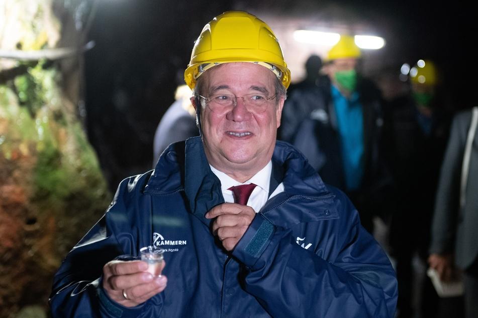 """Armin Laschet (CDU), Ministerpräsident von Nordrhein-Westfalen, hält im Bergwerk """"Zinnkammern Pöhler"""" unter Tage ein Glas Schnaps."""
