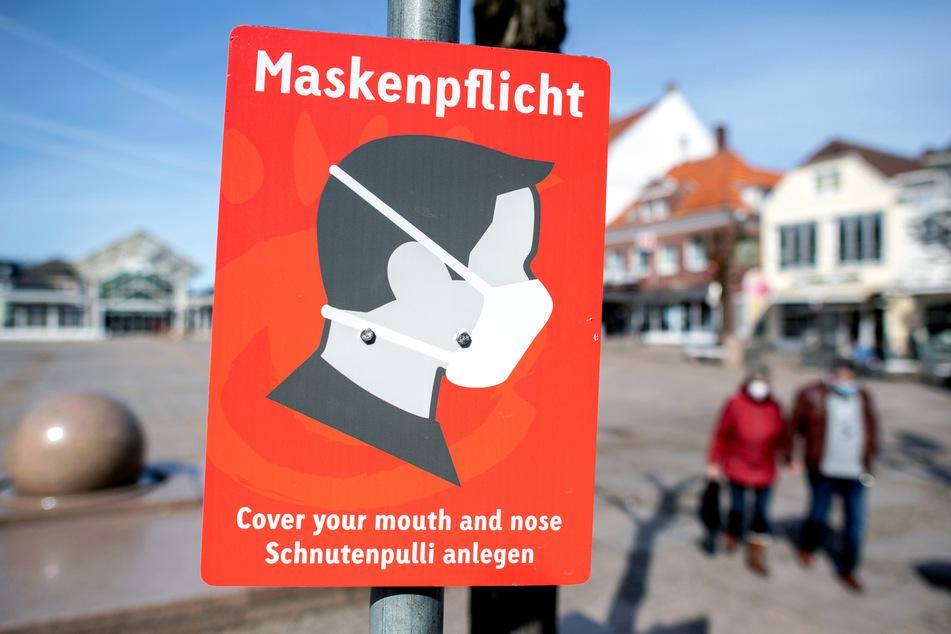 Ein Schild in der niedersächsischen Stadt Aurich weist auf die geltende Maskenpflicht hin.