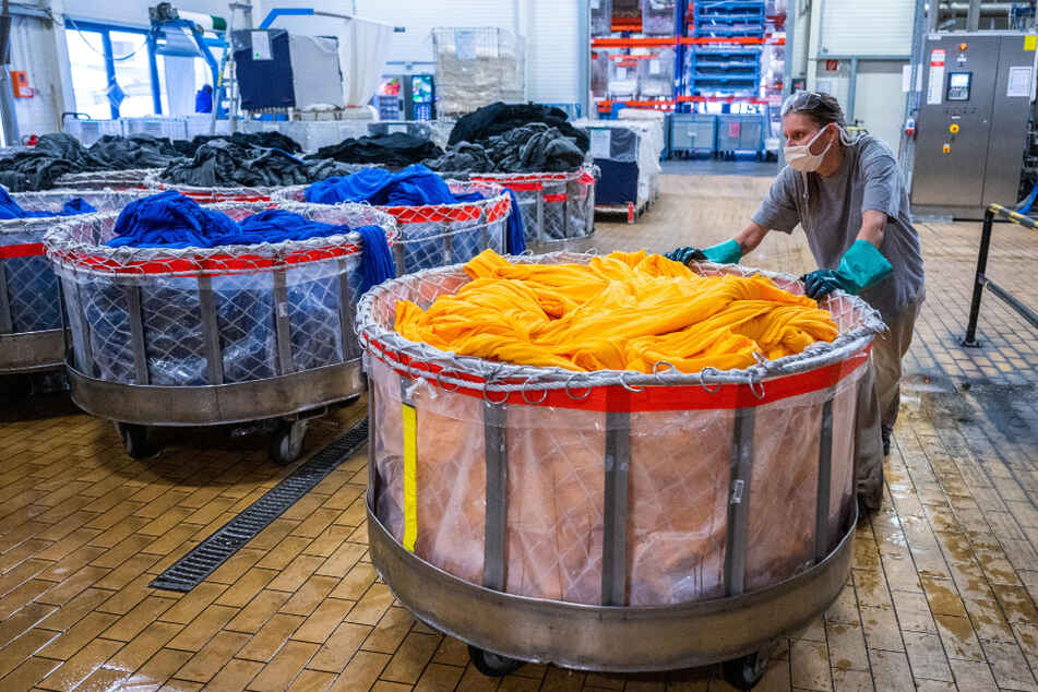 Eine Mitarbeiterin von pro4tex transportiert gefärbte Stoffbahnen für die Mehrweg-Masken.