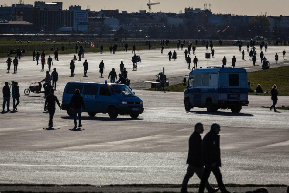 Polizeiwagen fahren zwischen Spaziergängern auf dem Tempelhofer Feld. (Symbolbild)
