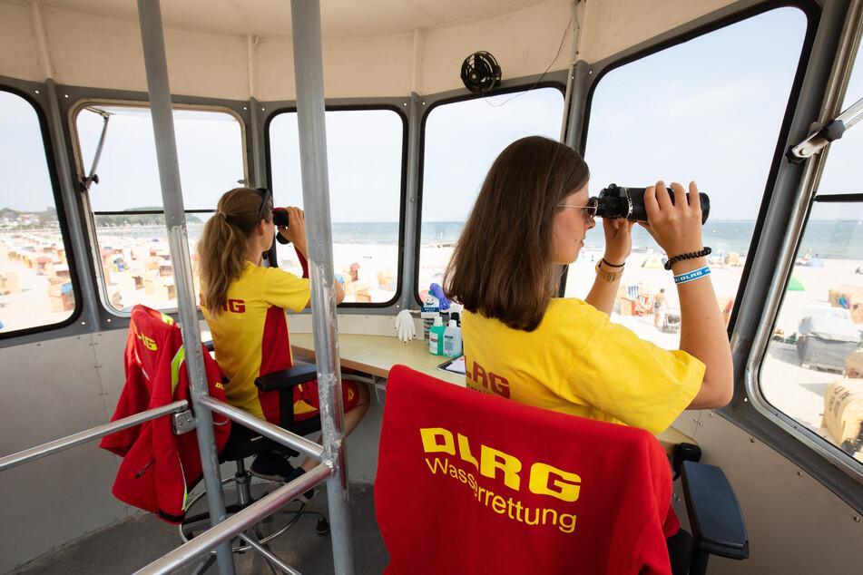 DLRG-Rettungsschwimmerinnen beobachten auf einem Wachturm den Strand und das Wasser in Travemünde.