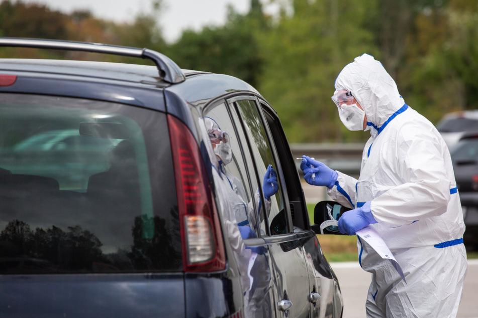 Neuenburg am Rhein: Ein Mitarbeiter des DRK im Schutzanzug steht am geöffneten Fenster eines Autos während er auf einem Autobahnparkplatz den Abstrich für den Corona-Test durchführt.