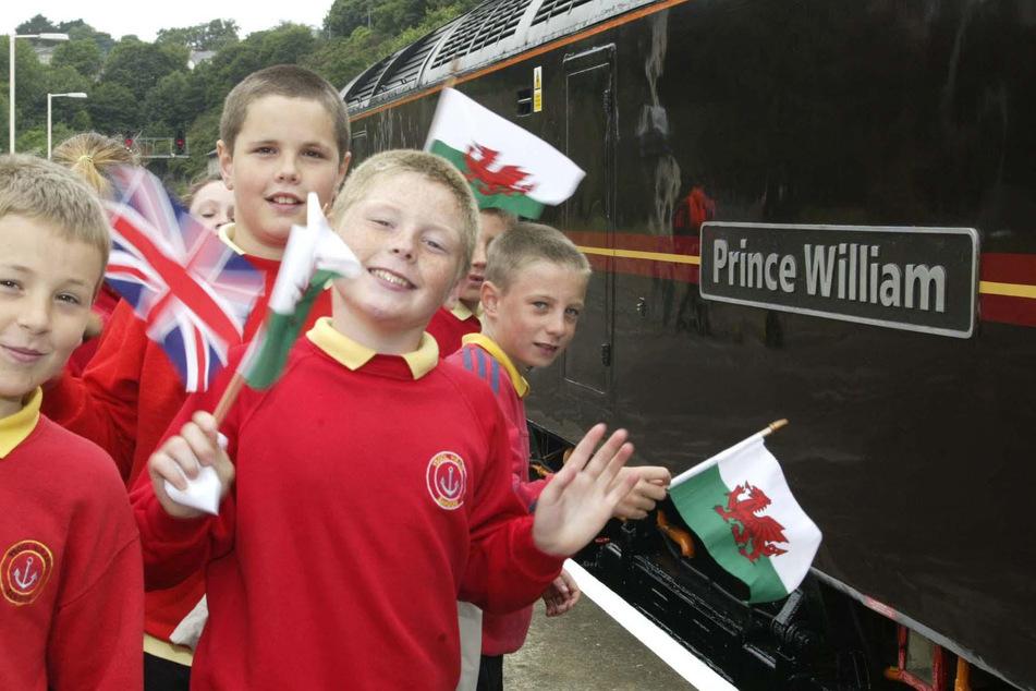 """Schulkinder aus Bangor heißen den Königlichen Zug willkommen, der von der """"Prince William""""-Lokomotive gezogen wird, die Prinz William und sein Vater der Stadt anlässlich seines 21. Geburtstags gekauft haben."""