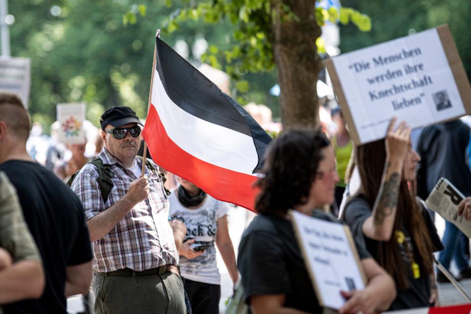 Bei einer Demo in Berlin am Samstag trägt ein Teilnehmer eine Flagge des Deutschen Reiches.