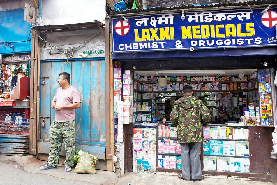 Ein Mann steht an einer Apotheke in Indien. (Symbolbild)