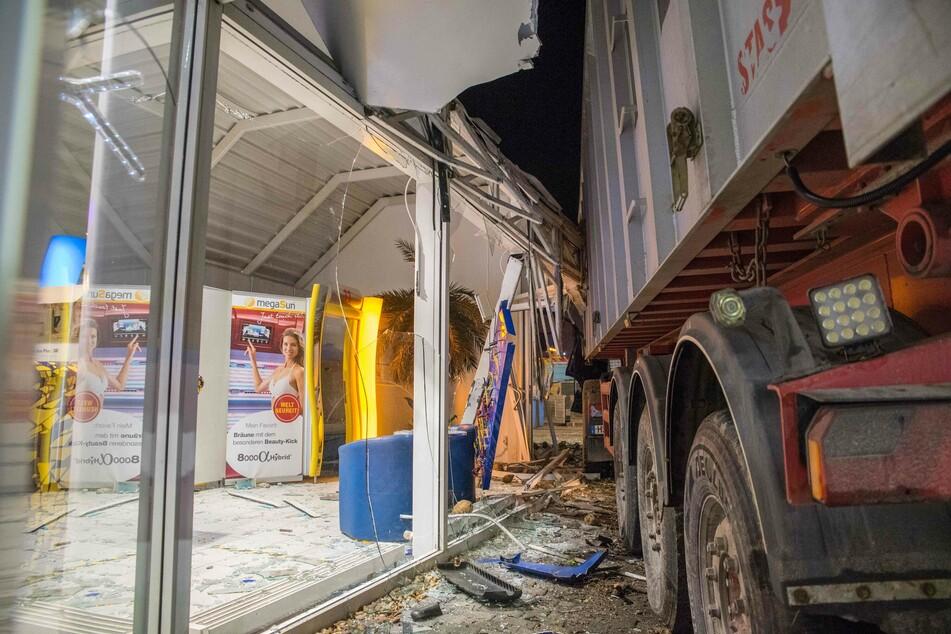Durch den Zusammenprall fuhr der Lastwagen in die Front eines Sonnenstudios und beschädigte auch dieses erheblich.