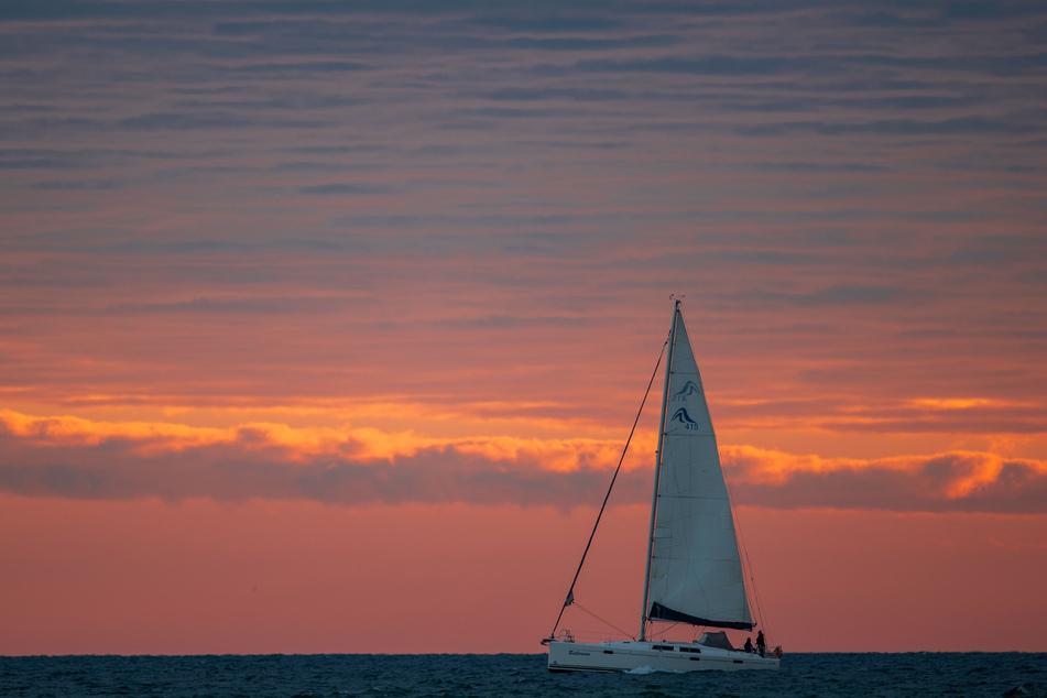 Ein Segelboot ist vor Sonnenaufgang auf der Ostsee unterwegs. Für Urlauber aus Mecklenburg-Vorpommern können Hotels und Ferienwohnungen wieder öffnen.
