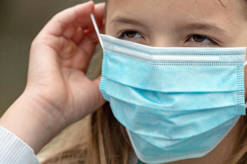 Eine Grundschülerin setzt sich vor dem Betreten eines Schulgeländes eine Einweg-Maske auf.