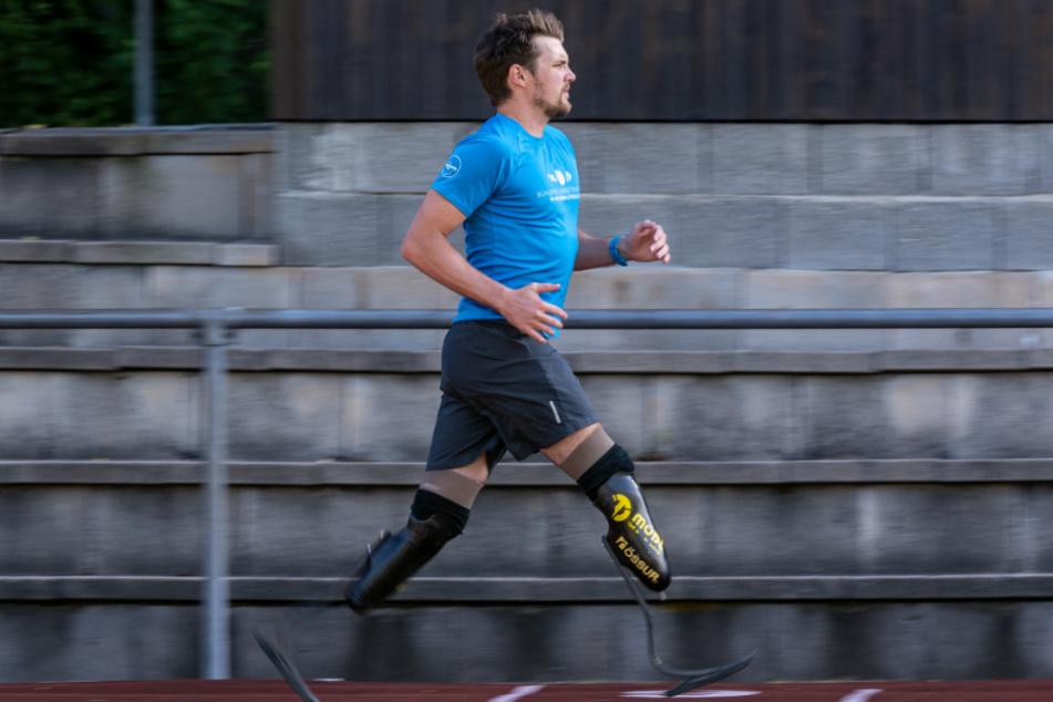 Maximilian Schwarzhuber läuft auf einem Sportplatz. Der 28-jährige hat sich beide Unterschenkel amputieren lassen und ist nun Extremsportler.