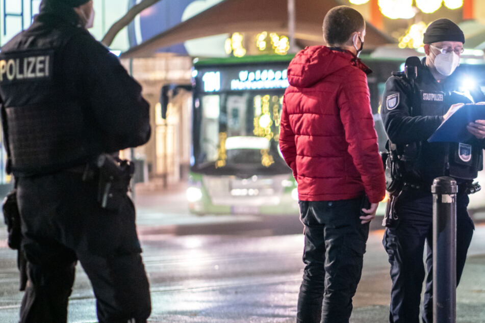 Polizisten nehmen um Dezember in Offenbach die Personalien eines jungen Mannes auf.