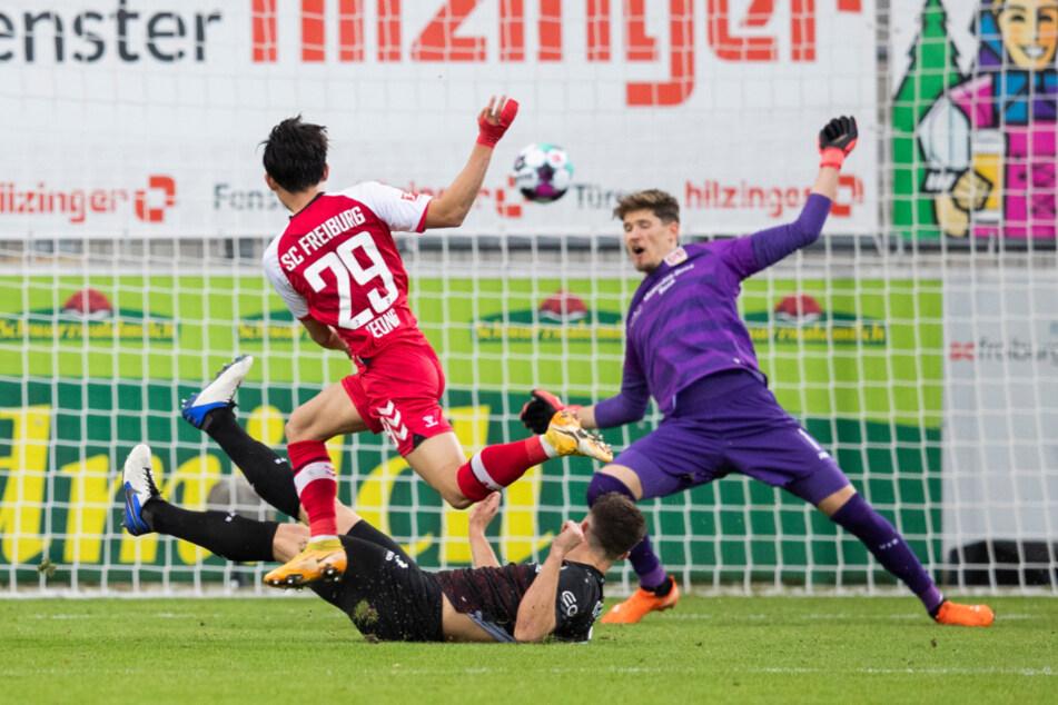 Freiburgs Woo-Yeong Jeong (vorne) überwindet VfB-Keeper Gregor Kobel (r.) und erzielt das 2:1 für den SC.