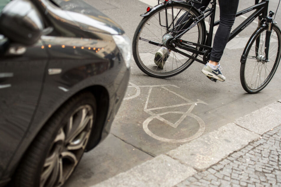 Eine Radfahrerin umfährt ein auf dem Radweg stehendes Auto.