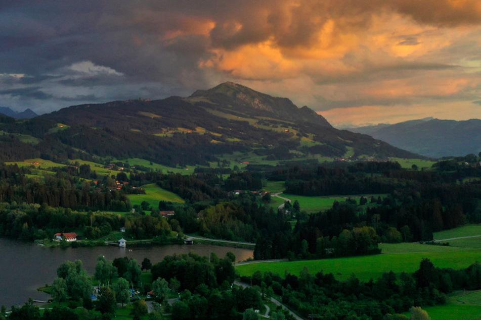 Das Licht der untergehenden Sonne färbt den Himmel über dem Rottachsee und dem Grünten.
