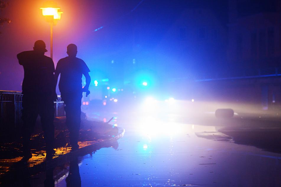 Zwei Männer laufen an einer Straße in Bad Schandau, die von der Kirnitzsch geflutet wurde.