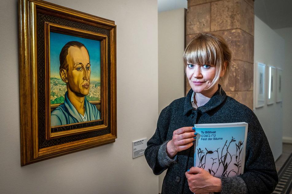 Kuratorin Karoline Schmidt vor einem Porträt des Chemnitzer Kunstsammlers David Leder von Gustav Schaffer aus dem Jahr 1920.