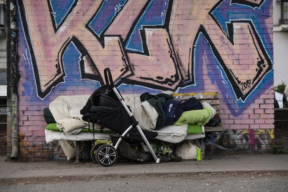 Ein Obdachloser schläft auf einer Bank unweit des Landwehrkanals in Berlin.