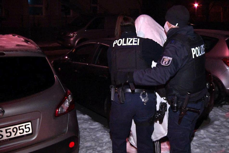 Die Polizei führt einen 23-Jährigen ab, der an der Tat beteiligt gewesen sein soll.