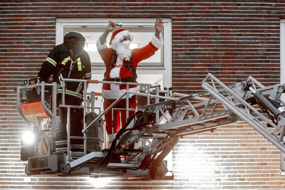 Professor Martin Rupprecht, leitender Oberarzt in der Kinderorthopädie des Altonaer Kinderkrankenhauses, fährt als Weihnachtsmann verkleidet mit Hilfe der Feuerwehr zu einem Fenster des Krankenhauses.