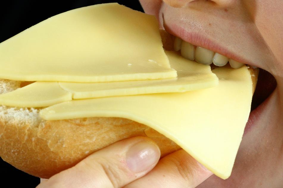 Eine Frau isst ein mit Käsescheiben belegtes Brötchen. (Symbolfoto)