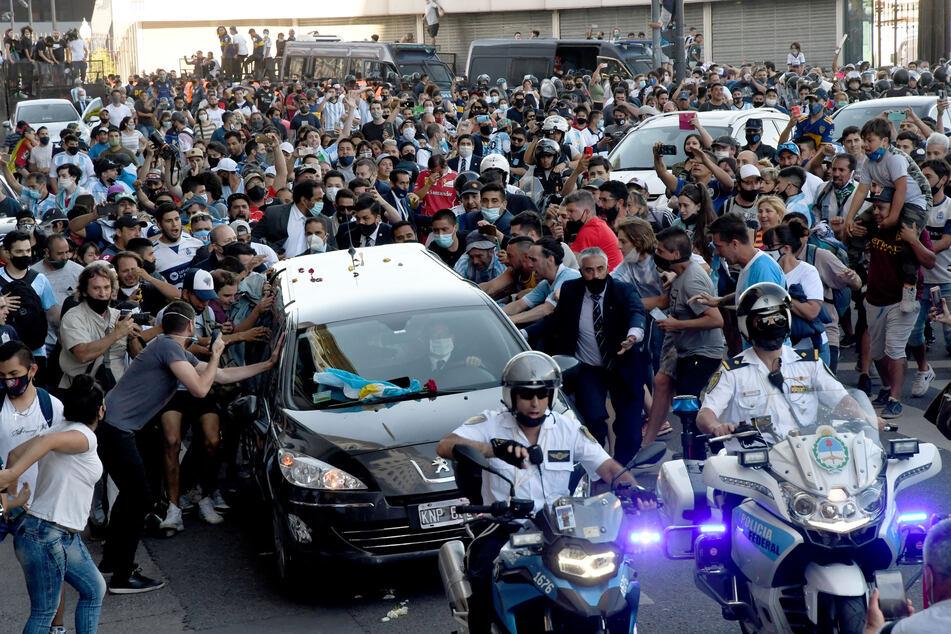 Der Leichenwagen mit den sterblichen Überresten von Diego Maradona verlässt das Regierungsgebäude begleitet von Fans.