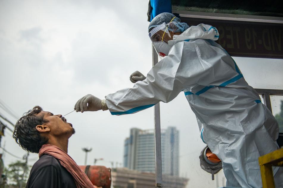 Ein Mitarbeiter des Gesundheitswesens (r) in Neu-Delhi nimmt bei einem Mann für einen Corona-Test einen Nasenabstrich.