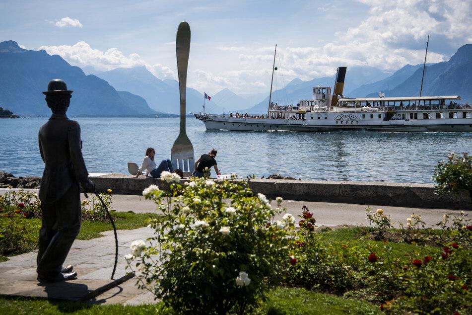"""Das Passagierschiff """"Vevey"""" der Compagnie generale de navigation sur le Lac Leman (CGN) fährt auf dem Genfersee an der """"Fourchette de l'Alimentarium"""" und einer Statue von Charlie Chaplin vorüber."""