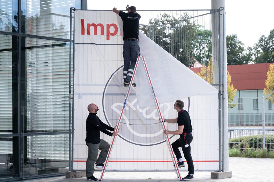 DRK-Logistiker entfernen vom Impfzentrum auf der Messe Dresden das große Transparent. Nach gut acht Monaten wird die Einrichtung nun geschlossen.
