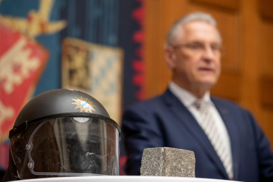 Joachim Herrmann (63, CSU), Innenminister von Bayern, steht hinter einem Polizeihelm, der beim G20-Gipfel 2017 in Hamburg durch einen Pflasterstein beschädigt wurde.