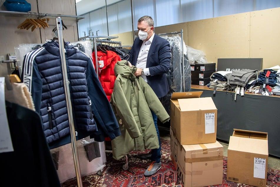Jens Ristedt sortiert im Lager seines Modehauses die unverkaufte Winterkleidung.