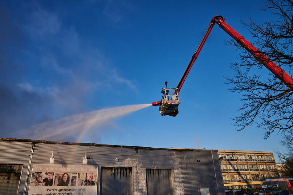 Von Drehleitern aus versuchen Feuerwehrleute einen Hallenbrand in Marienfelde zu bekämpfen.