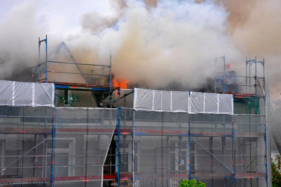 Das Dach des Mehrfamilienhauses steht in Flammen.