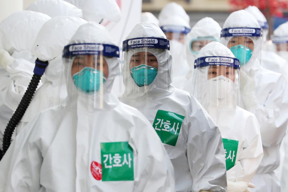 Krankenschwestern in Schutzkleidung stellen sich in einer Schlange auf, bevor sie das Dongsan-Krankenhaus für die Behandlung von neuen Coronavirus-Patienten betreten.