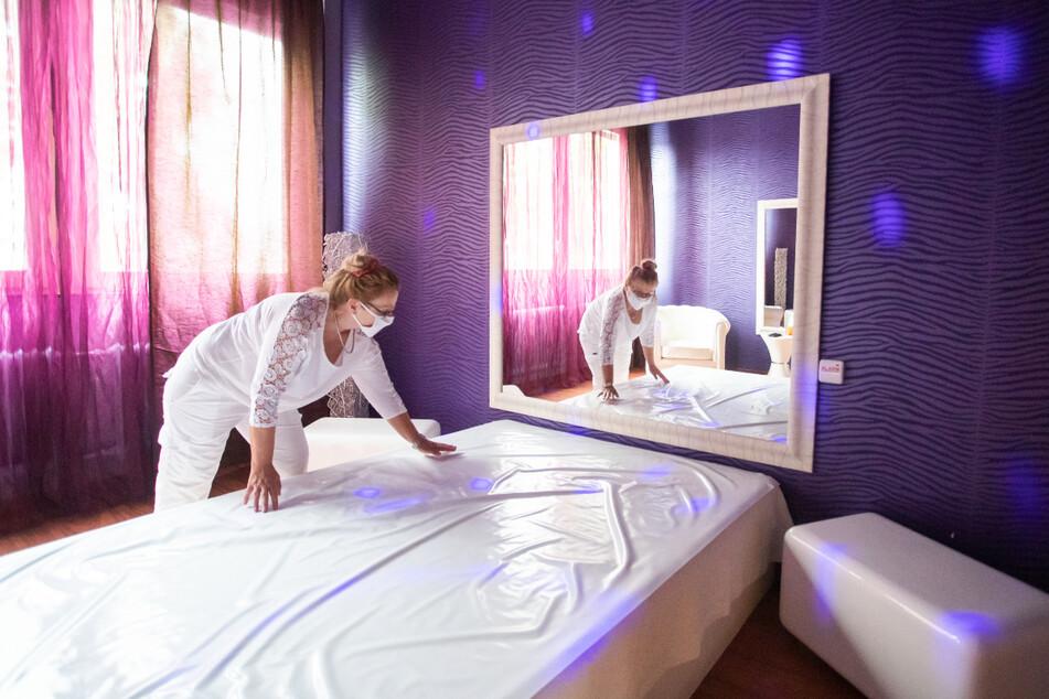 """Karlsruhe: Laura, Mitbetreiberin von """"Lauras Girls"""", richtet ein Bett in einem Arbeitszimmer des Bordells für die Wiedereröffnung."""